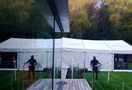 Party tent reflected in the glass house