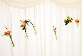 Flower sprigs in simple glass bottles hanging on a wire attached to the marquee frame