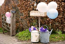 Vintage style wedding entrance, with signpost and watering cans