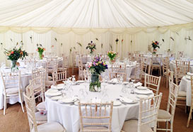 Wedding marquee looking pretty with sprigs of flowers in bottles