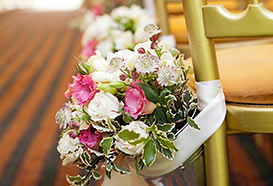Pretty bouquets in buckets attached to chairs on either side of the aisle
