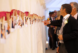 Guests view photos of the couple growing up, hung by clothes peg to a swag
