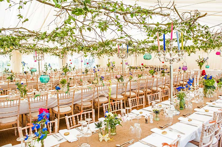 Vintage wedding marquee anches attached to wires and swathed with leaves colourful natural flowers lined up trestle tables junglespirit