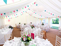Colourful bunting strung across the roof of a marquee