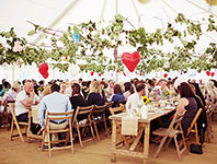 Wedding tent with dark wood tables and wooden chairs